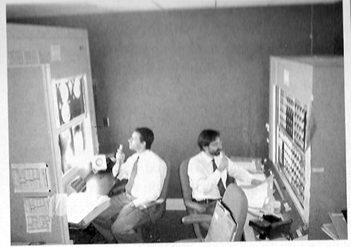 "Carlos Amato (left) learning to ""read"" conventional film in 1999 to understand various problems and limitations associated with existing ""hybrid"" reading rooms in which conventional film-based readings are performed on lightboxes adjacent to digital softcopy workstations."